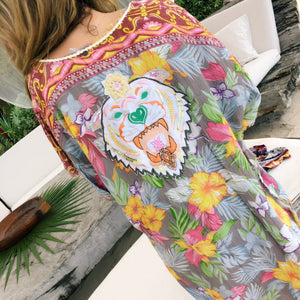 Bring in the sunshine with lots of color and funkiness! Our new Good Karma Cover Up is a beautiful floral print with an embroidered Bengal Tiger on the back of it with sequin details.  The bright yellow, pink, and purple coloring make a statement for all your upcoming fun in the sun plans. The braided edging around the top of the cover up runs around to the front attached with two tassels on both ends for the complete funky boho detail.  100% Viscose