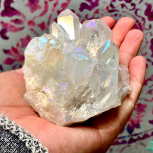 Angel Aura Quartz Crystal is bonded with Silver and Platinum giving it a prismatic iridescence.  This stone is known to elevate your mood with peacefulness and tranquility, possessing a sweet and loving energy.  Angel Aura Quartz has high levels of spiritual energy that is beneficial to your aura. - Angel Aura Quartz - Wildflower Long Island