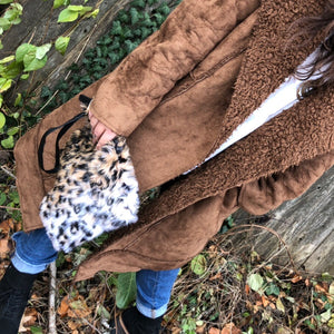 "Feeling fierce?  This is faux fur leopard print clutch is the perfect addition to your outfit.  With vegan leather wrist strap.  Measures 10"" x 8"""