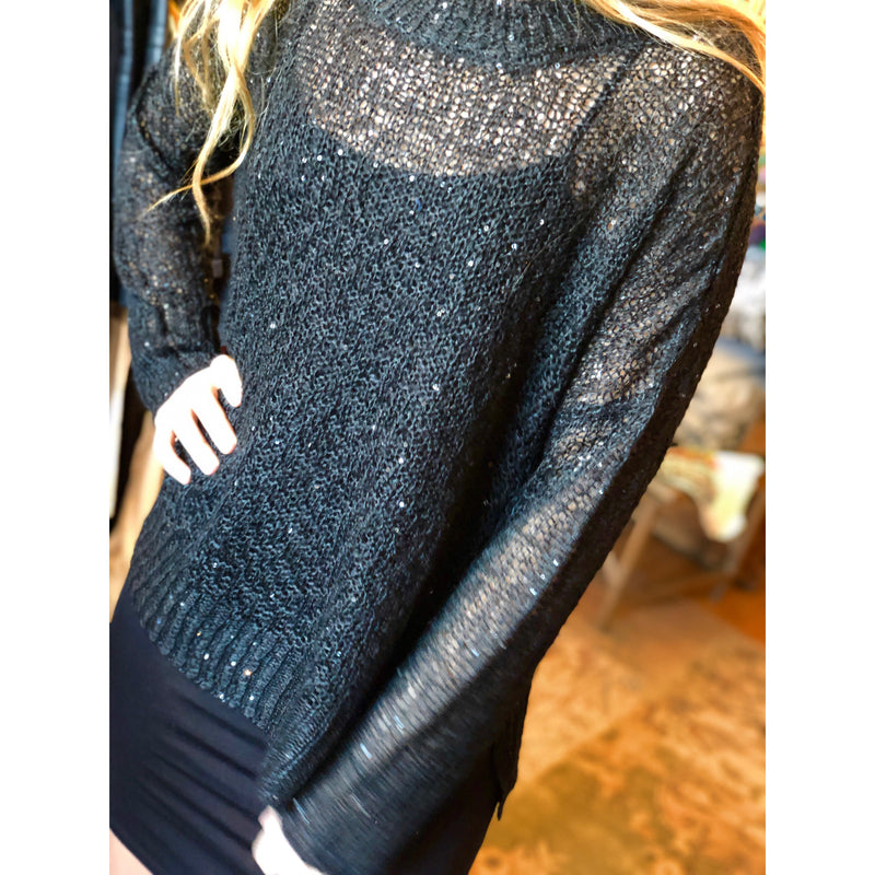 Twinkling sequins illuminate the night in this beautiful Black Knit Kerry Sweater, a must have top made by Band of Gypsies.  The hi-lo detail adds a whimsical touch to this lightweight knit. A perfect choice for your favorite denim for a casual look, you can easily transition this top into any evening outfit.
