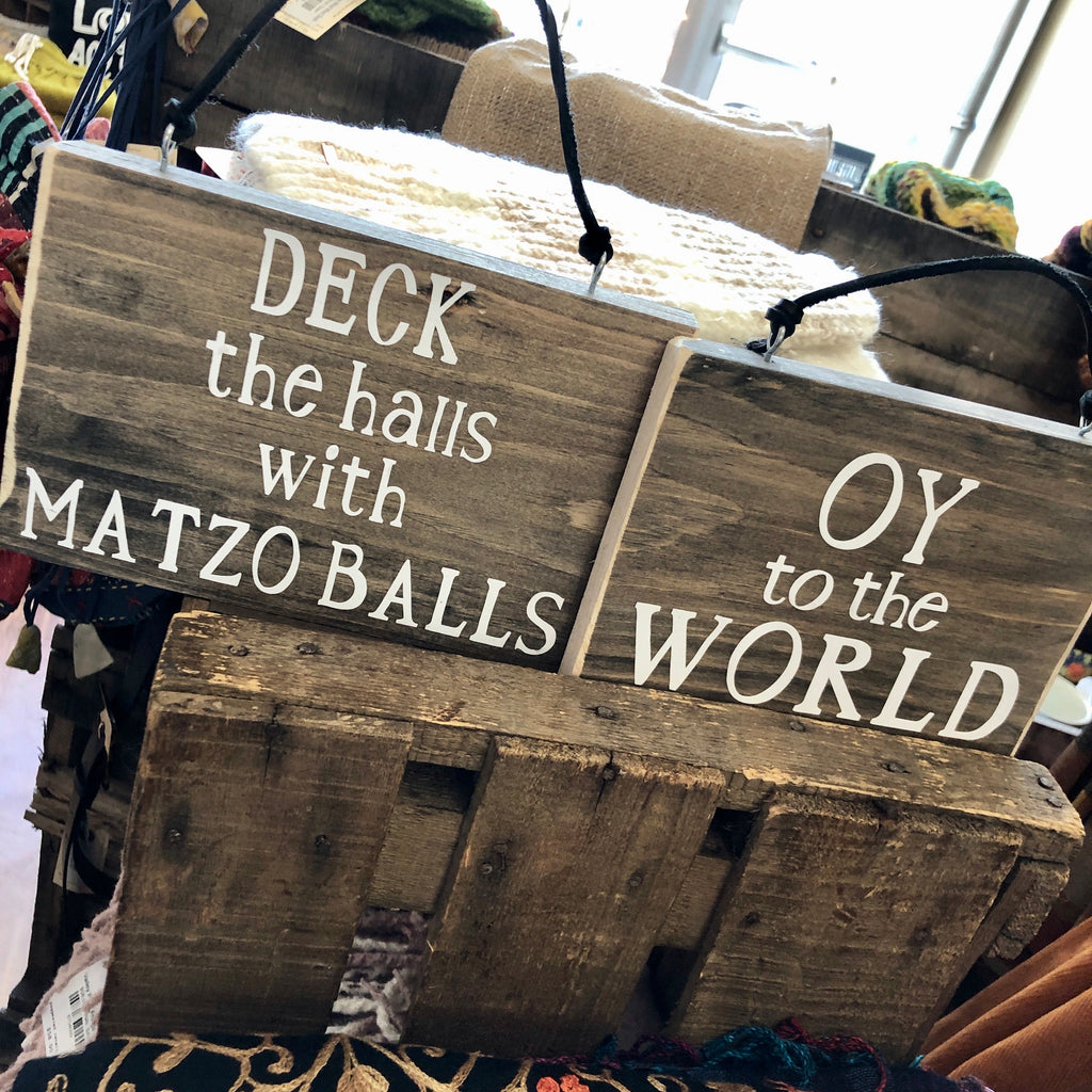 "Oy To The World!  Give the gift of a giggle with our Hanukkah Wood Wall Signs, handmade with distressed wood by a local Long Island artisan, these hilarious signs are strung on a black leather cord.  Oy To The World measures 7.5"" x 5.5""  Deck The Halls With Matzo Balls measures 8.5"" x 5.5"""