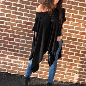 We've voted this top #1 as a closet staple.  The Pure Black Poncho off the shoulder poncho features an asymmetrical hemline and has sleeves so you can easily wear it with a jacket.  95% Rayon.  5% Spandex.
