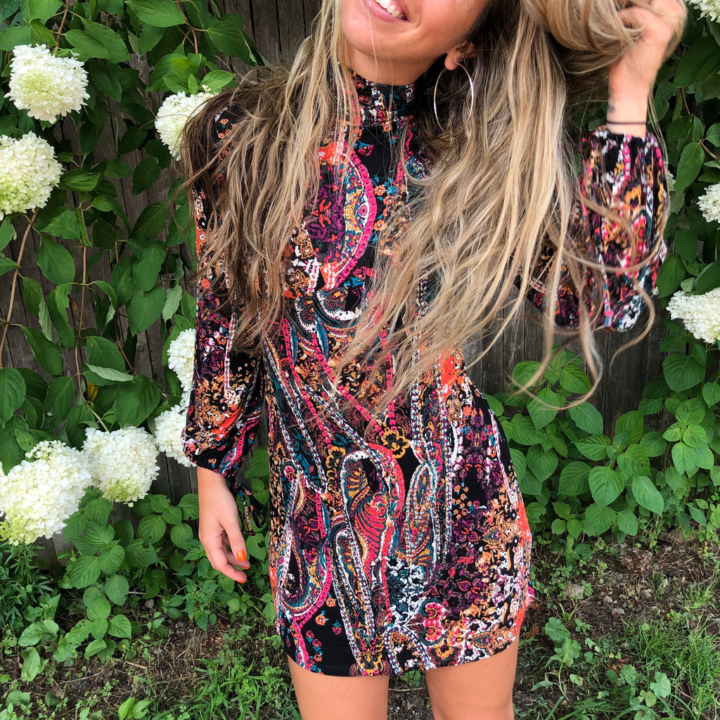 Feminine, free spirited and bohemian. Our Free People dress in print and color totally gives the retro vibe you want this season. This head turning mini dress flows in a soft jersey fabric, mock neck, tie wrists and a cut out back.  We absolutely love this one!  95% Rayon 5% Spandex