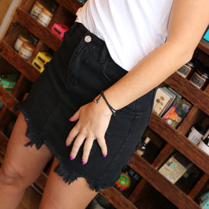 Our new Queen Black Denim Mini Skirt is a MUST have. This is the perfect mini silhouette with destroyed rip details throughout, finishing with a raw cut frayed hem. Back and front pockets with a button fly.  88% Cotton, 12% Polyester