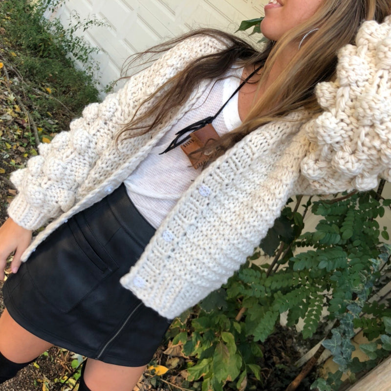 Add the perfect amount of femme to your outfit in the Handmade Chunky Sweater.  Thick knit-knots detail the oversized sleeves giving a pom pom effect.  Maintain a more sophisticated style and button up with three hidden front snaps.   70% Acrylic.  30% Wool.