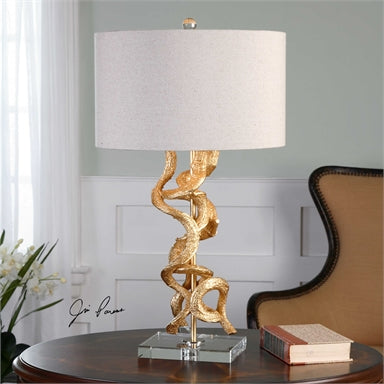 Inspired from real twisted vines, this lamp has a bright gold leaf finish accented with a thick crystal foot and matching finial. The round hardback drum shade is an oatmeal linen fabric.