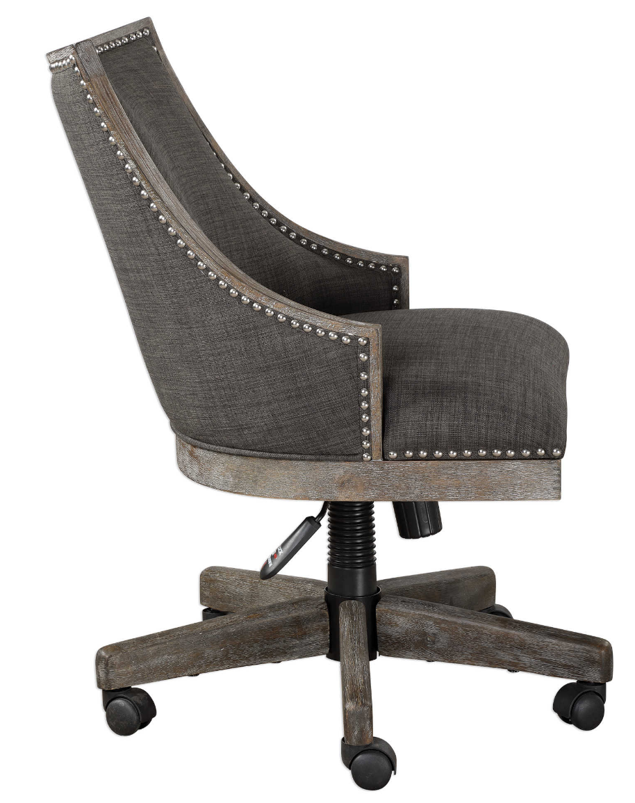 The Steward Office Chair has a curved back design in warm charcoal gray linen, accented by polished nickel nailhead trim. Honey stained frame is finished with a heavy gray wash.