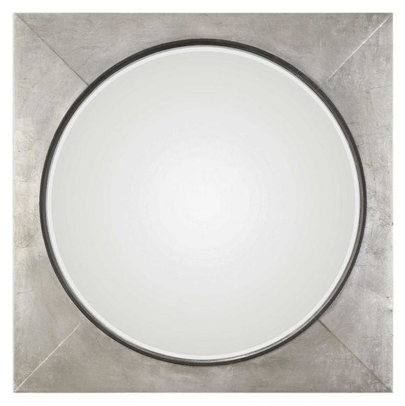 The Introvert Wall Mirror is modern and simple. Heavy iron frame finished in a hand applied metallic silver leaf, accented with a raised rustic black center. Mirror features a generous 1 1/4