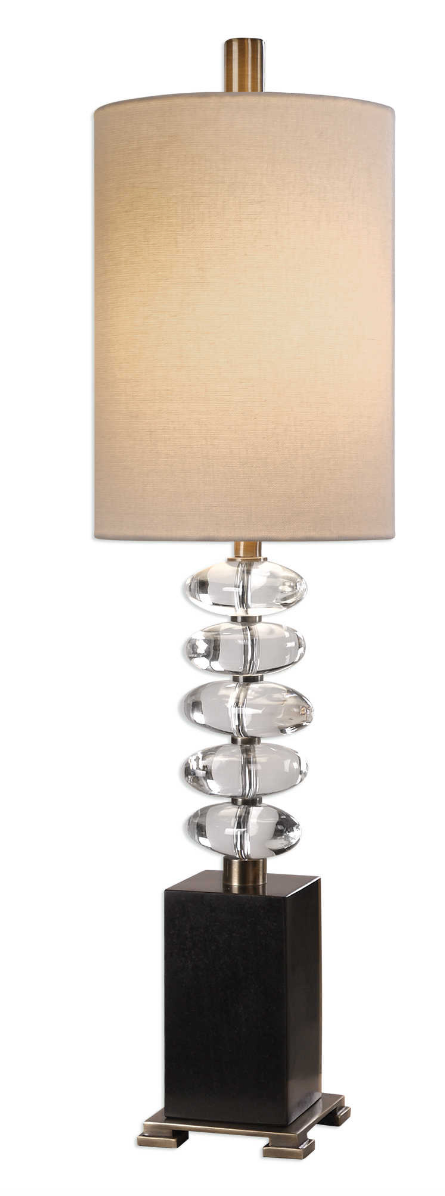 The Clearstone Table Lamp Is big on style and design. Stacked, thick crystal eggs, separated by antique brass steel columns, displayed on a chunky black marble foot. The tall round hardback shade is a light beige linen fabric. Add a unique edge to your lighting.