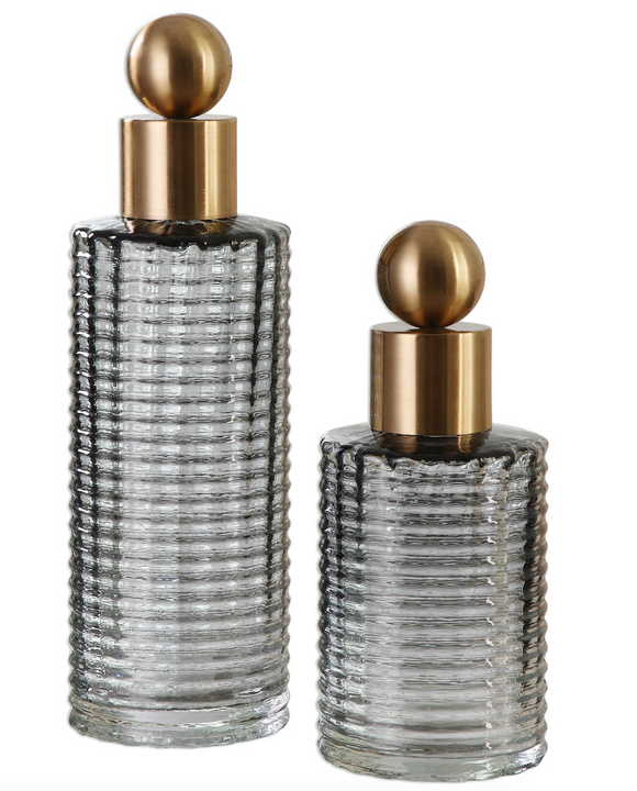 The Decador Decorative bottle set is a great additions to any modern space. Create a soothing display with these glass bottle's elegant ribbed design in light charcoal accented with sophisticated brushed brass tops. For decorative purposes only.