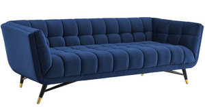 Embolden your living room décor with the Tipper Modern Sofa. Featuring a blend of chic, contemporary, and mid-century modern design, It's broad profile, deep seating, generous tufting, stain-resistant velvet polyester upholstery, flared armrests, and subtle metal accents imbue rich detail and chic sophistication