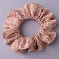 top view of ruffled hair scrunchie in coral and cream leaf print