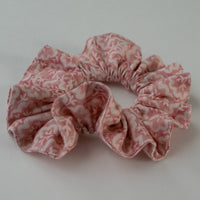 side view of ruffled hair scrunchie in coral and cream leaf print