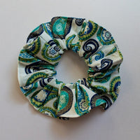 Top view of medium ruffled hair scrunchie in jewel tone blue green paisley with gold highlights on white background