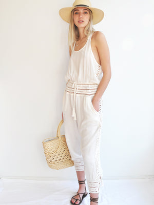 Anna Kosturova Relaxed fit romper with handmade crochet inserts at the waist and as the leg cuffs with incased button closure, embellished with tassels. Unique and comfortable festival look.