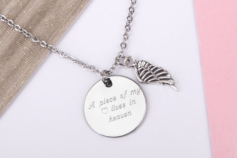 Silver Coloured Necklace with Silver Coloured 'A piece of my heart lives in heaven' Disc Pendant plus Silver Coloured Angel Wing charm