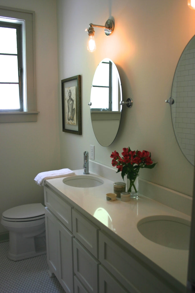This bathroom needed to function for two people- so we removed the old linen cabinet, added two vanities, custom cabinetry, and a new tub/shower!