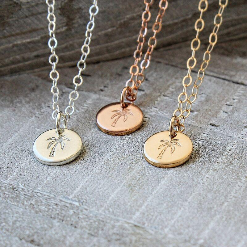 This image features a pendant necklace with a palm tree stamp in your choice of sterling silver, 14k rose gold or gold.