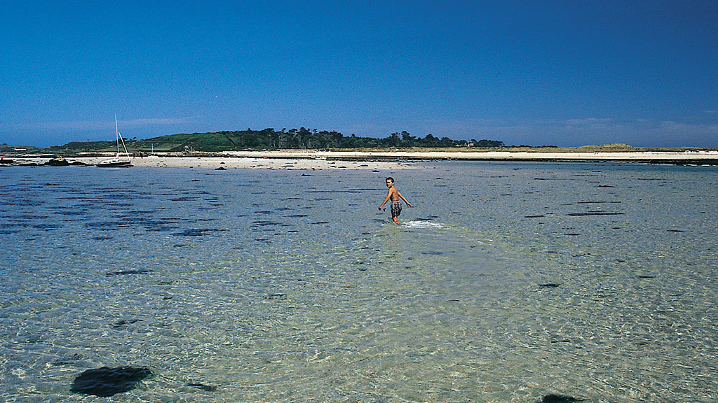 Boy wading between Samson and Tresco, Isles of Scilly