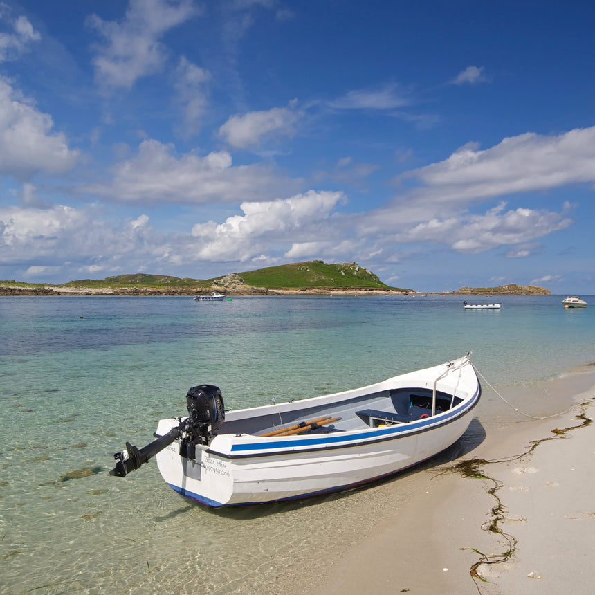 Photo from Friendly Guides Isles of Scilly Guidebook showing a boat at The Porth, Lowertown on St Martin's, Isles of Scilly. In the background Great Hill on Tean.