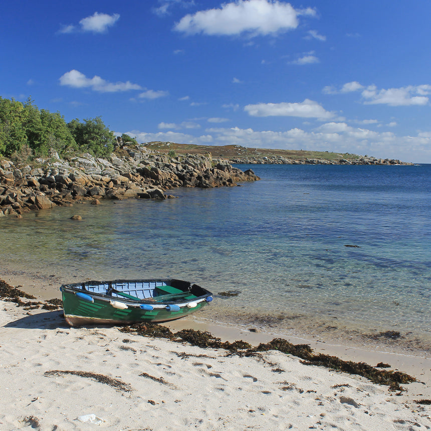 Photo from Friendly Guides Isles of Scilly Guidebook showing boat at Cove Vean on St Agnes, Isles of Scilly. In the background is Gugh.