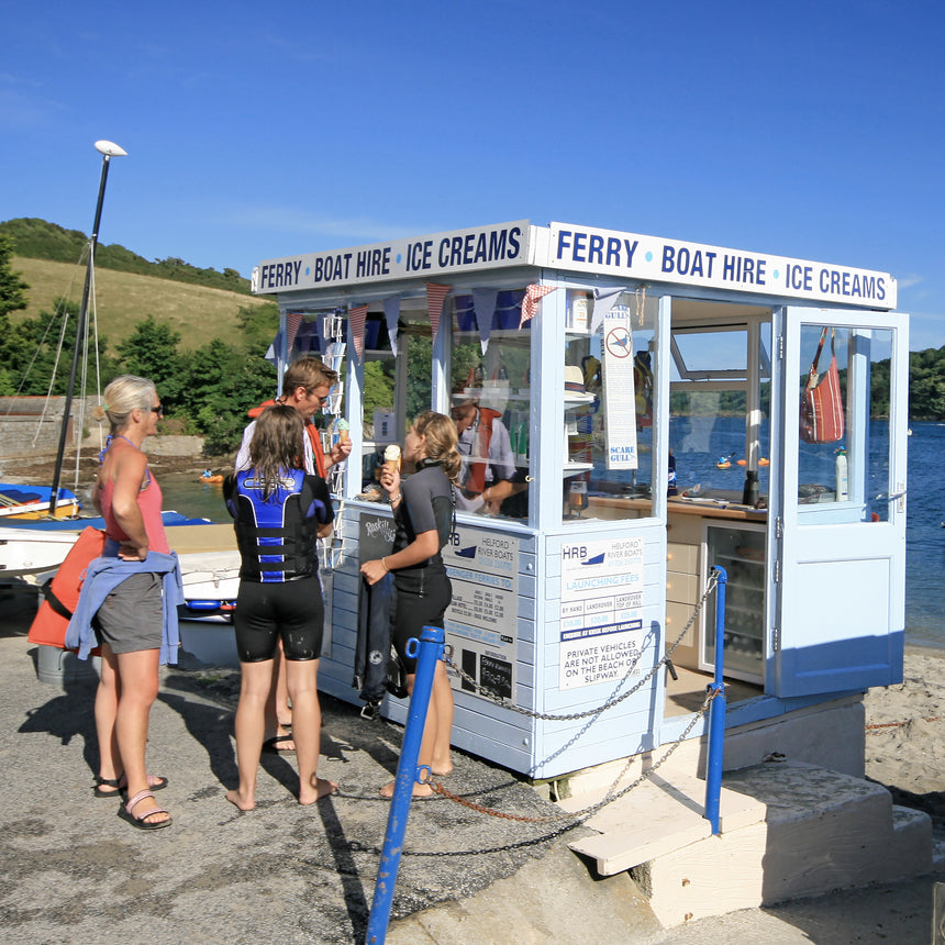 Photo from Friendly Guides Helford Guidebook of people buying ice creams at the ferry kiosk for Helford River Boats at Helford Passage