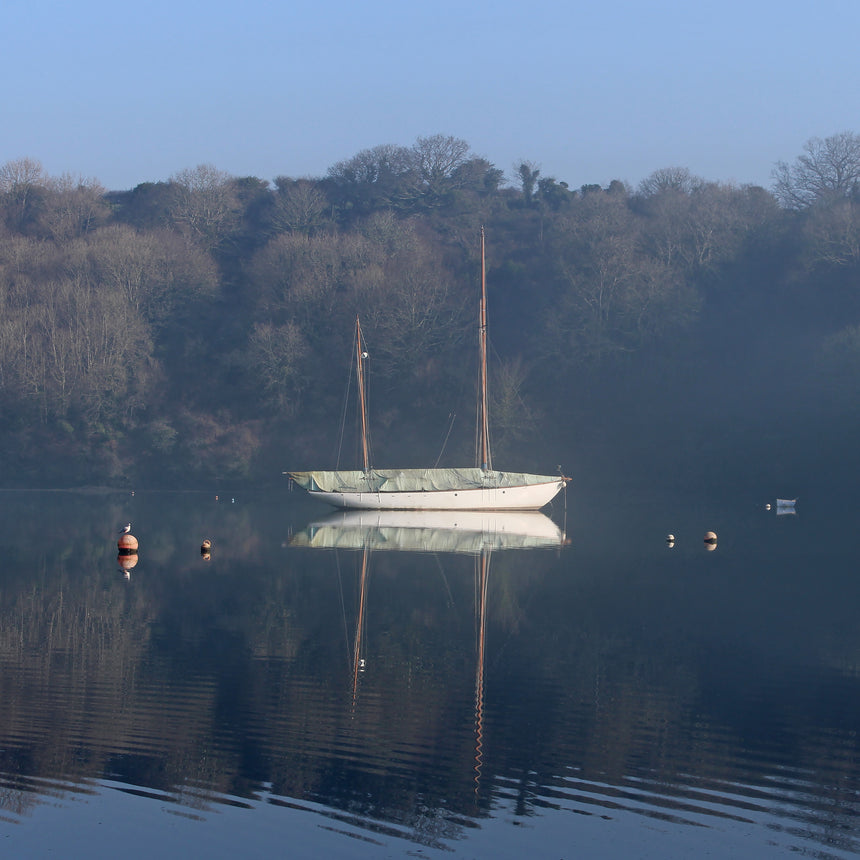 Photo from the Falmouth and the Roseland Guidebook showing a yacht moored in Cowlands Creek near Trelissick