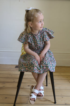 Girls floral dress, girl siting on chair wearing floral dress