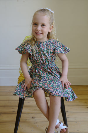 Girls floral dress, girl sitting on chair wearing floral dress