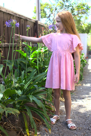 Girls pink dress, girl wearing pink dress standing in garden