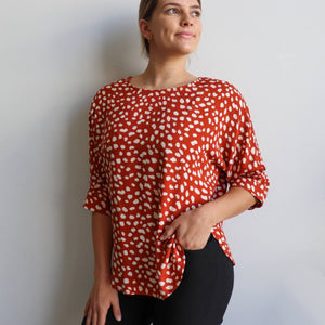 Avoca women's blouse in a spotted print pattern. Loosely cut summer top with scalloped hemline and 3/4 length sleeve with button detail. Made in a quality rayon fabric. Sizes 8-16. Rust.