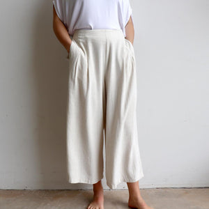 Stradbroke Pants 3/4 length wide-leg women's pants. Made with neat front pleats, two side pockets & elasticated at back of waistband for comfort. Easy care linen/viscose fabric blend. True to fit sizing, available in 8-18. Natural.