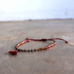 Threaded bracelet with cut glass beads featuring fine, mini tassel. Great for stacking or individual wearing. Slide-knot adjustable closure provides sizing flexibility. Shiraz.