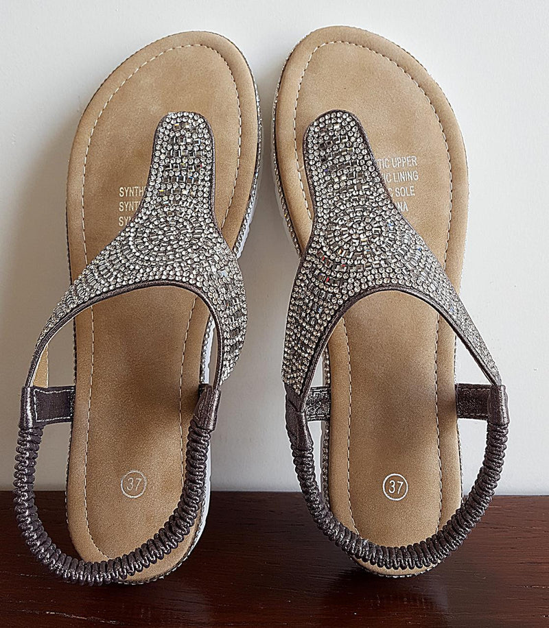 An easy slip-on summer sandal with lots of bling! Soft gel padded sole + elastic ankle strap. Silver.