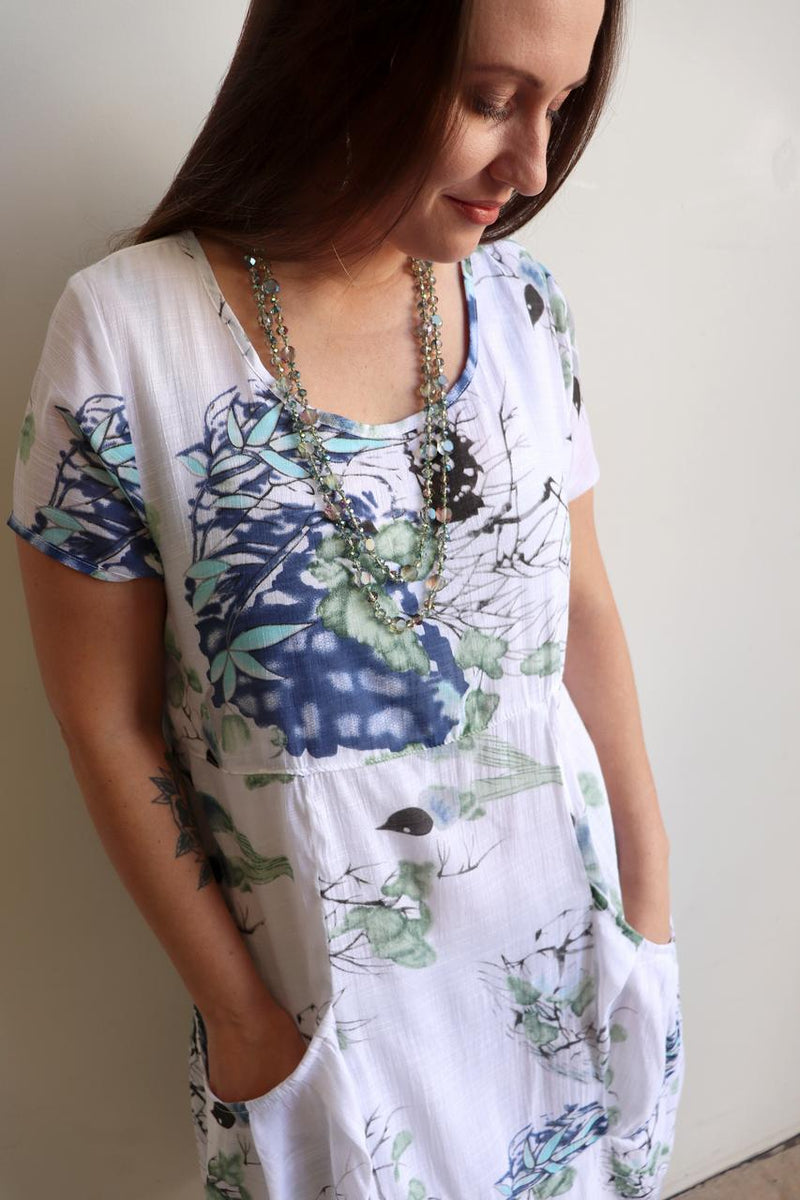 Womens trans seasonal shift tunic dress with short sleeves and two front/side pockets. Flattering cut to the knee with subtle waist shape detail in a beautiful floral watercolour print.  Plus size available up to a 22.