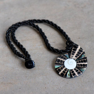By The Sea Shore Necklace made with mother-of-pearl and glass beads in a tortoise shell pattern. Shell-Black.