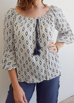 Womens light 100% rayon peasant style 'Casablanca' summer blouse with circular flounce 3/4 sleeve, elastic neckline + tassel tie feature on front. White + navy Ikat print.