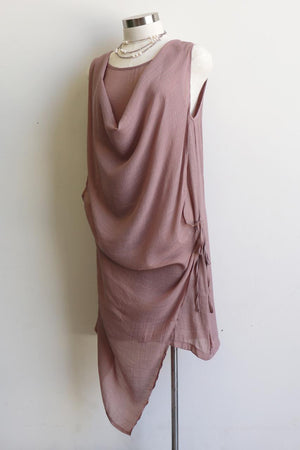 Lightly textured soft + floaty cowl neck tunic dress with draping middle panel that ties on one side. Easy, low-maintanance cotton blend sleeveless summer dress perfect for holidays in the sun. Sizes 8 > 20 available. Oyster Pink.
