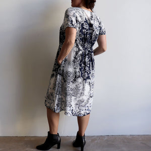 The Charlie Shift dress is a smart-casual, short sleeve shift dress in an elegant navy blue print and below-the-knee hemline. Back view.