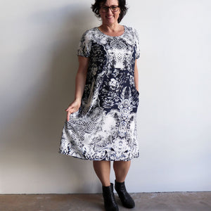 The Charlie Shift dress is a smart-casual, short sleeve shift dress in an elegant navy blue print and below-the-knee hemline. Long view.