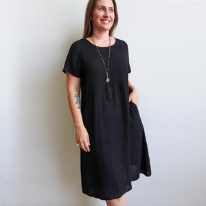 Short-sleeved, below-the-knee summer dress in a loose shift style. Made with a soft linen blend fabric with sizes small to plus size. Black.