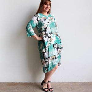 All season tunic style women's dress. Designed with roll-up sleeve, side pockets + below the knee hemline. Made from a softly draping rayon. Sizes 8-18. Teal Green.