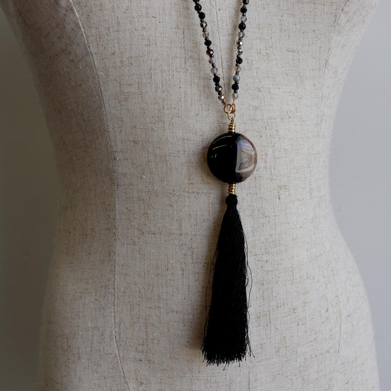 Delta Necklace is handmade with cut glass beads and a semi precious stone pendant with tassel.
