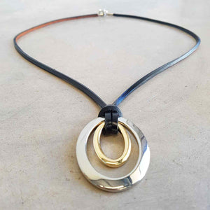 Medium-length leather necklace with silver + gold double ellipse pendant.  Black