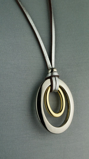 Medium-length leather necklace with silver + gold double ellipse pendant. Silver