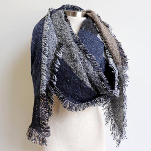 Fireside Wrap Scarf in plaid is a minky soft fibre winter knit accessory. Navy blue / charcoal. Wrapped view.