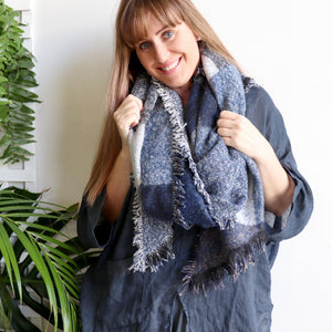 Fireside Wrap Scarf in plaid is a minky soft fibre winter knit accessory. Navy blue/charcoal on Laura.