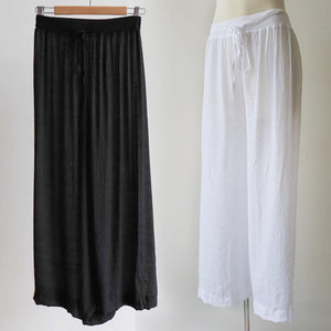 Women's wide-leg semi-sheer lounge beach pants with drawstring. Wear spring to summer on the hips or high waisted options. Great for tropical travel and casual floaty coast look. Plus sizes available up to a size 20 - White + Black.
