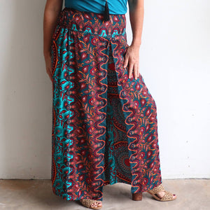 A lovely wrap pant made with cool, cotton feel 100% rayon with a fully elasticated back and neat, flat front for comfortable wear.  Available in two size options in a Turquoise-Rust colour.