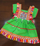Girl's Hill Tribe Tunic Dress with rainbow pompom trims and traditional tapestry. Green.